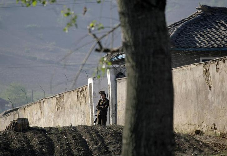 A North Korean soldier stands guard at the entrance of a women's prison near Chongsong, North Korea, May 31, 2009.