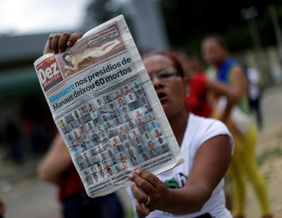 A relative of a prisoner holds a local newspaper, which shows a headline about a deadly prison riot, in front of Anisio Jobim prison in Manaus, Brazil, on January 3, 2017.