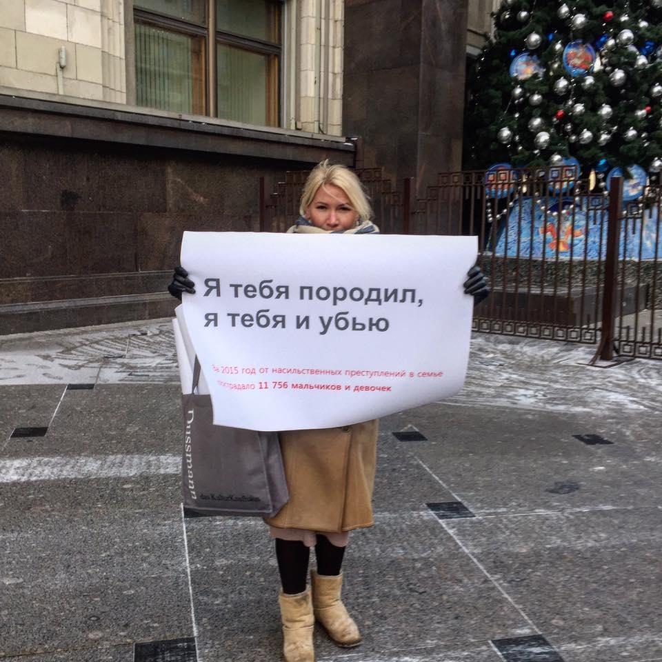 """Женщина на одиночном пикете против декриминализации домашнего насилия у здания Государственной Думы РФ с плакатом """"Я тебя породил, я тебя и убью. За 2015 год от насильственных преступлений в семье пострадало 11 756 мальчиков и девочек."""" Москва, 11 января"""