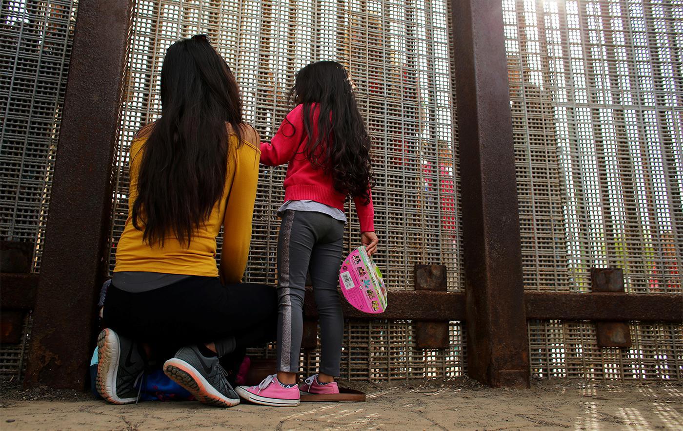 Члены одной семьи разговаривают между собой через заграждение на границе США и Мексики, Пограничный полевой парк, Калифорния, 19 ноября 2016 г.