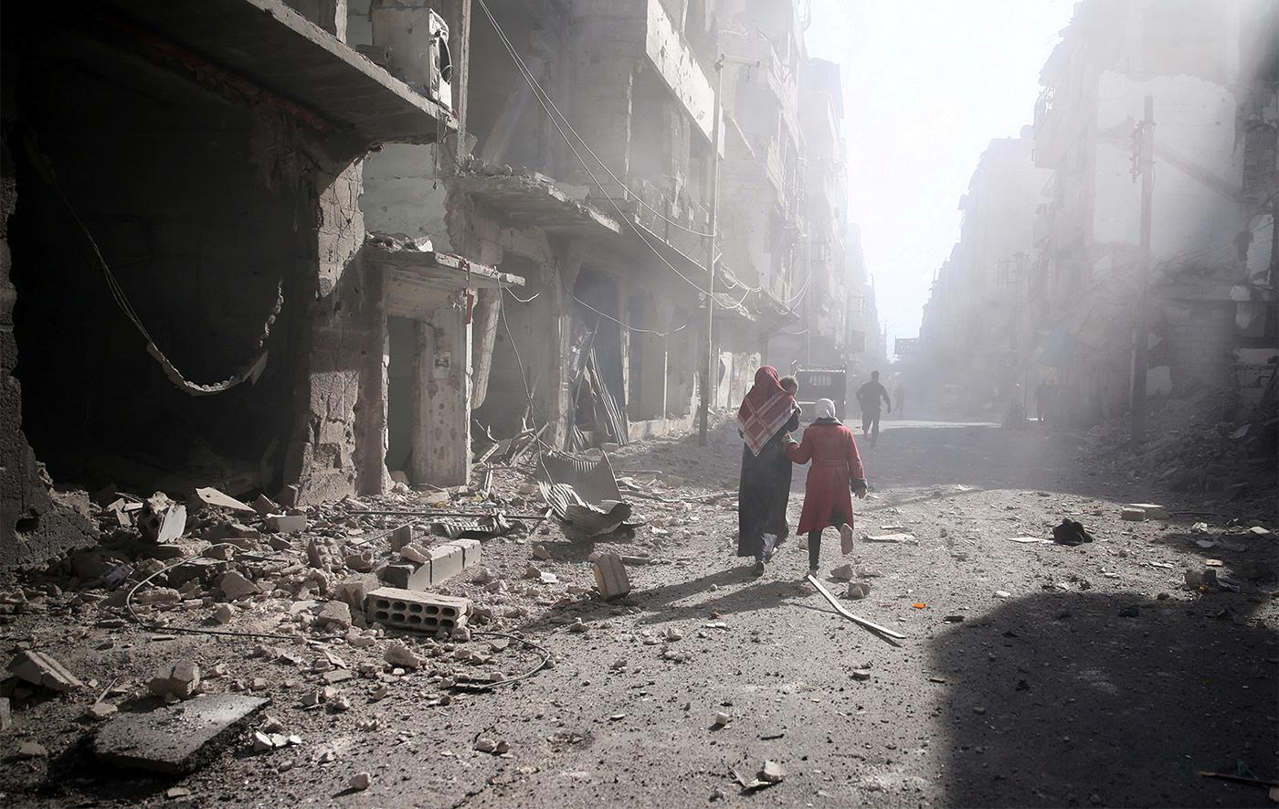 People walk past a damaged site after an airstrike in the besieged rebel-held town of Douma, eastern Ghouta in Damascus, November 2, 2016.