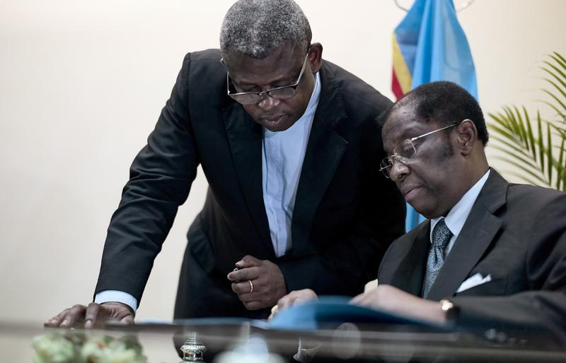 Congolese Justice Minister Alexis Thambwe Mwamba (right) is assisted by Abbot Donatien N'shole, CENCO secretary general, as he signs the accord between the opposition and the government of President Joseph Kabila at the Conference episcopale nationale du