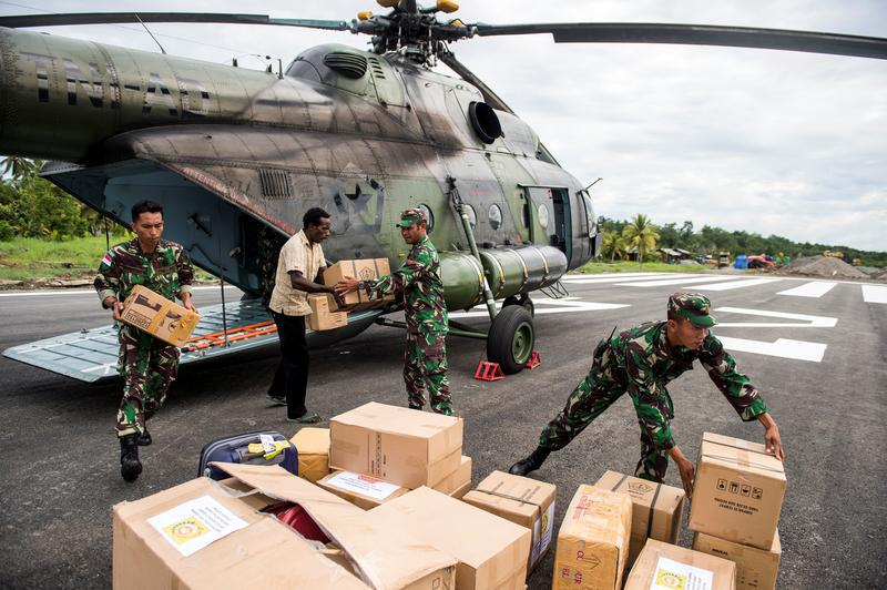 Indonesian soldiers along with a local resident unload food and medical aid in Ewer, Asmat District, in the remote region of Papua, Indonesia January 29, 2018 in this photo taken by Antara Foto.