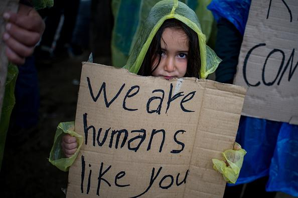 A girl holds a placard during a protest held by migrants and refugees to call for the reopening of the borders at a makeshift camp at the Greek-Macedonian border near the village of Idomeni