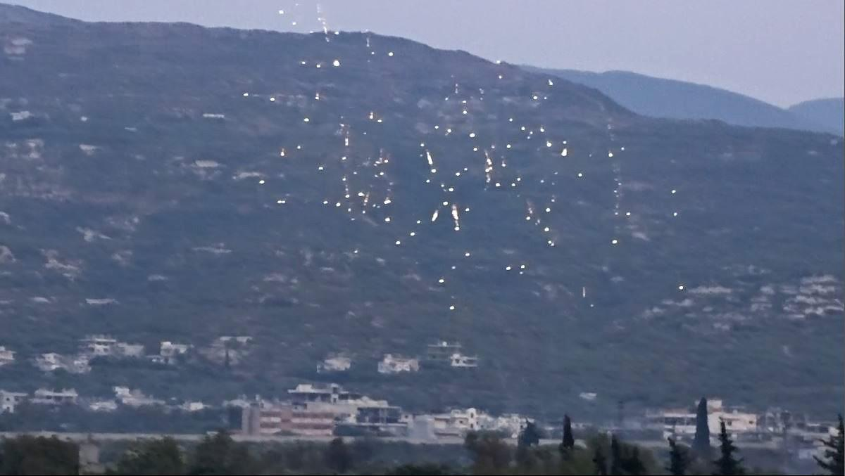 Incendiary rockets rain fire over farmland outside a town in western Idlib, Syria, on July 30, 2018.