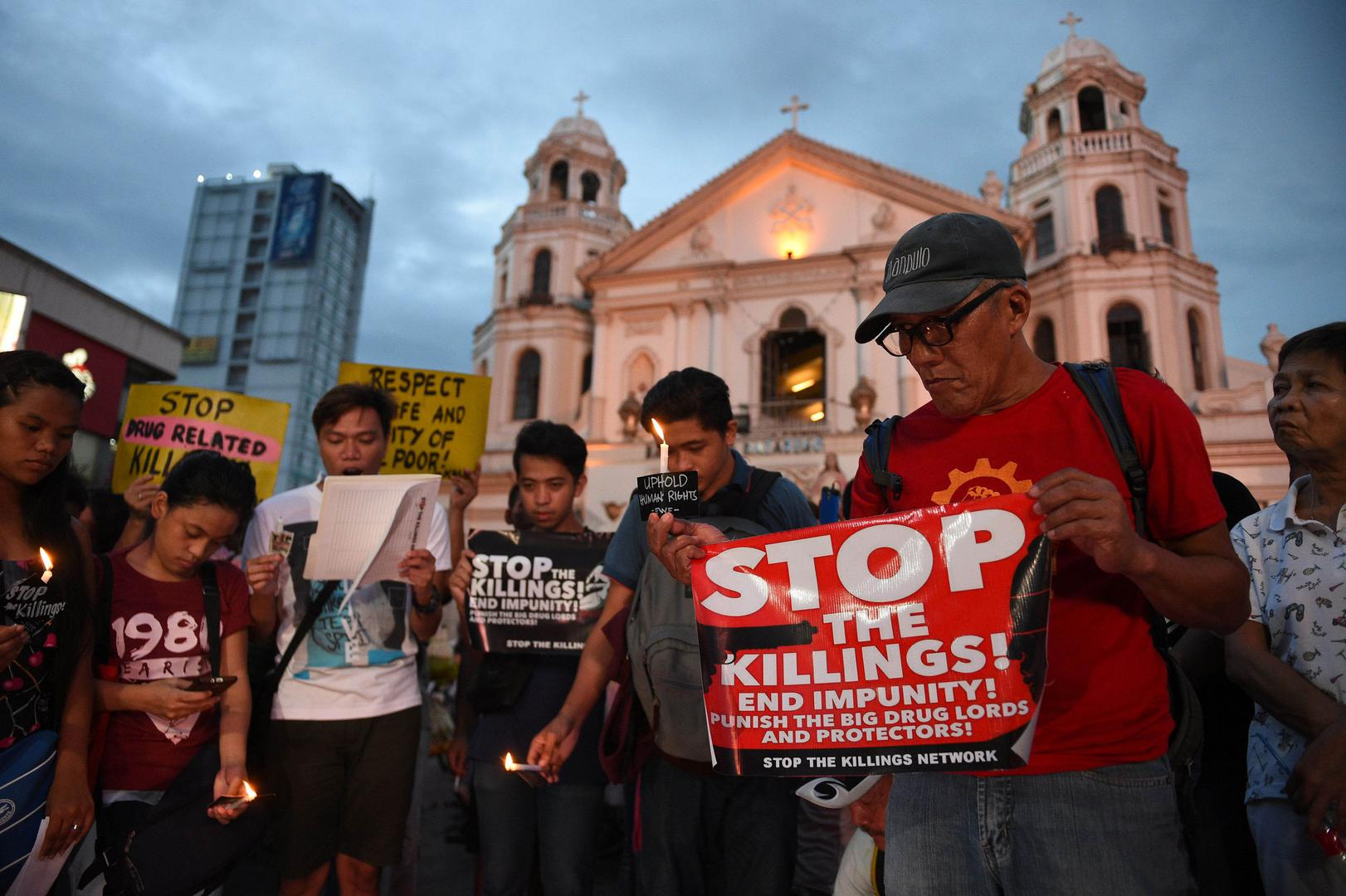 Activists hold a candle light vigil for victims of the extra judicial killings in the drug war of the government in front of a church in Manila on September 16, 2016