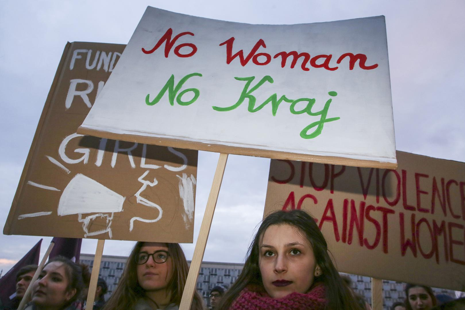 """Women's rights supporters at a demonstration for International Women's Day in Krakow, Poland, on March 8, 2018. The center sign uses the slogan """"No Woman, No Country."""""""