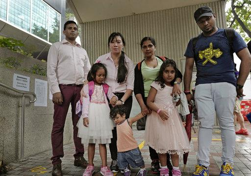 Asylum seekers, from left: Ajith Pushpa Kumara, Vanessa Mae Rodel and her daughter Keana, Nadeeka Dilrukshi Nonis and her son Dinath and daughter Sethmundi Kellapatha, and Supun Thilina Kellapatha, pose outside the building of Hong Kong's immigration depa