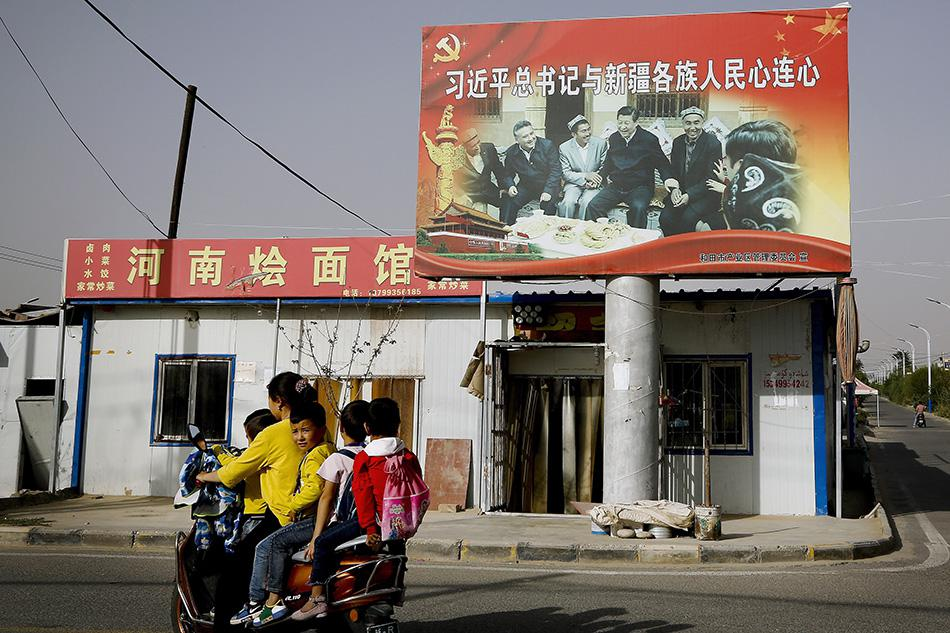 A Uighur woman picking up school children rides past a picture showing China's President Xi Jinping joining hands with a group of Uighur elders at the Unity New Village in Hotan, in western China's Xinjiang region.