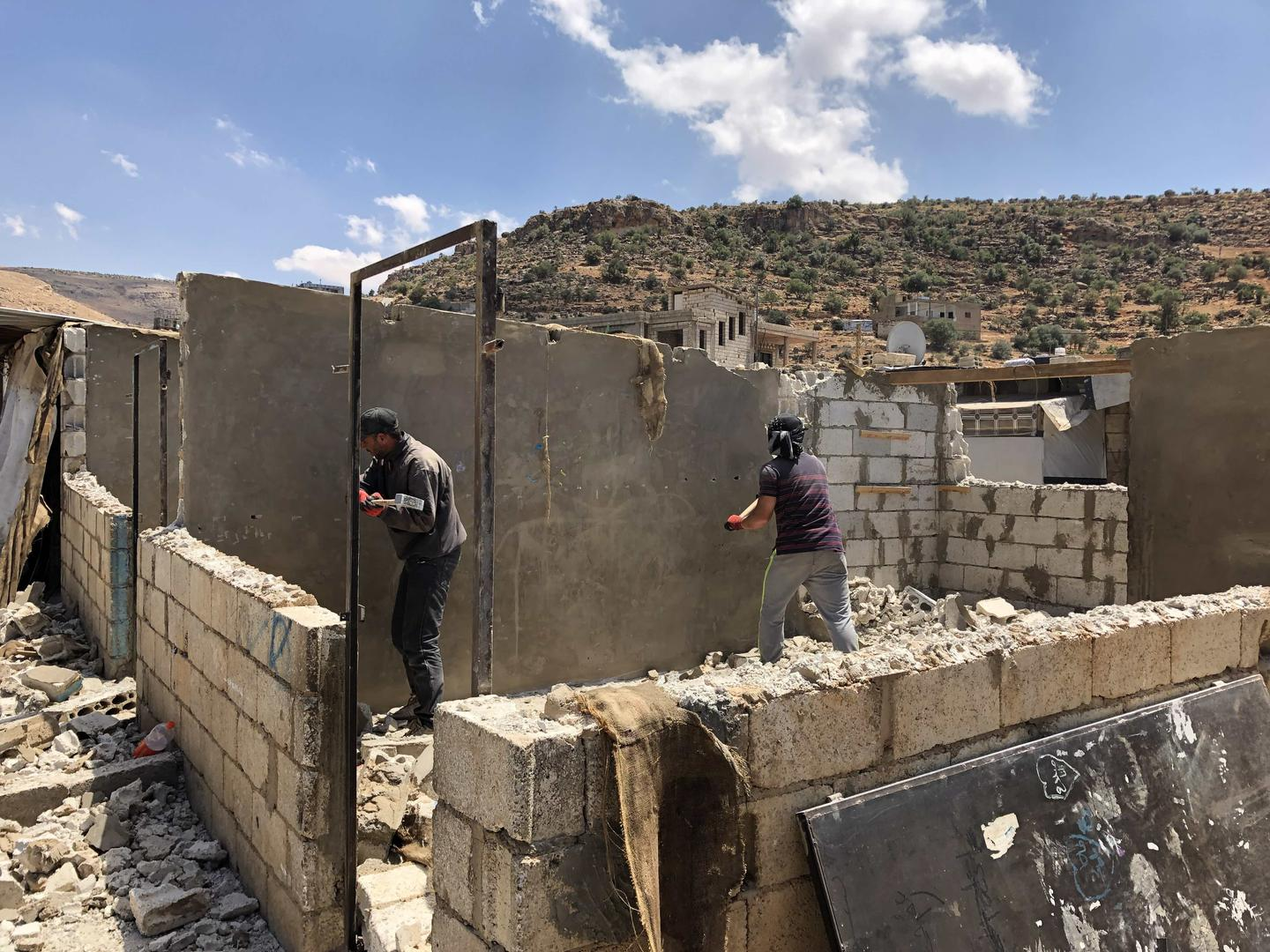 Men work to dismantle the walls of a shelter in a Syrian refugee camp in Arsal, Lebanon.