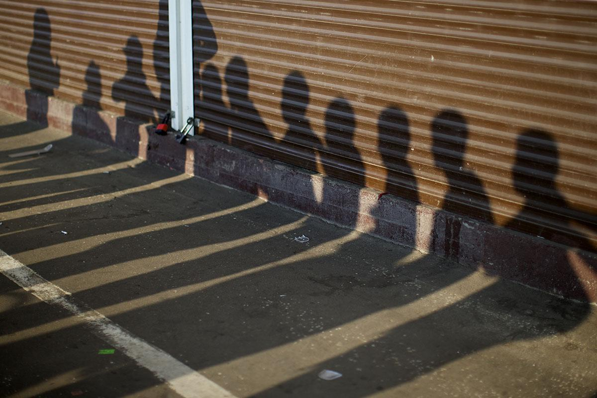 Shadows of people detained by Russian police, suspected of violating immigration rules during an action seen on containers at a street market in Moscow, Russia, August 7, 2013. © AP Photo/Alexander Zemlianichenko