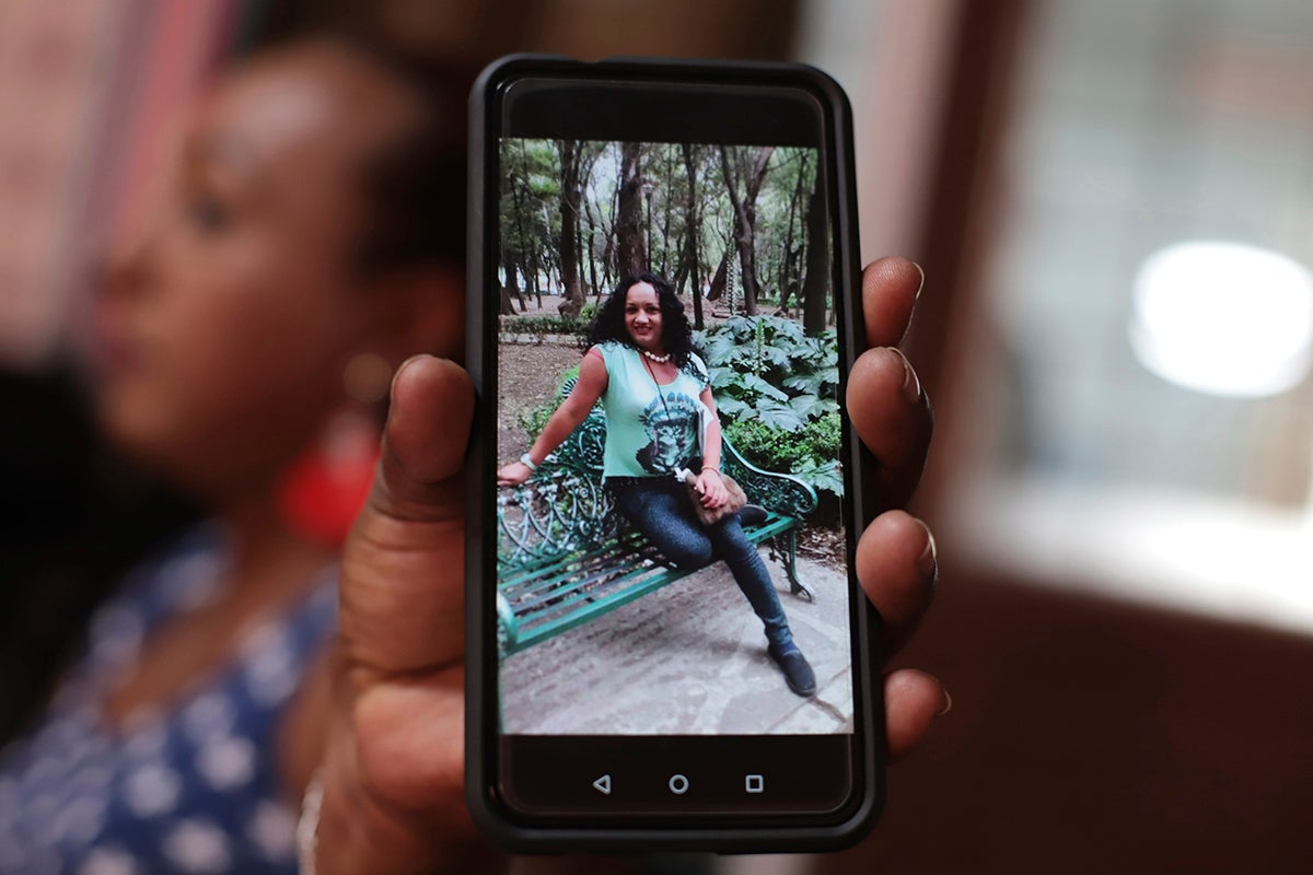 A transgender woman shows a photograph of Camila Díaz, whom she met while migrating to the US, where they both turned themselves in to immigration authorities. Both women were eventually deported.