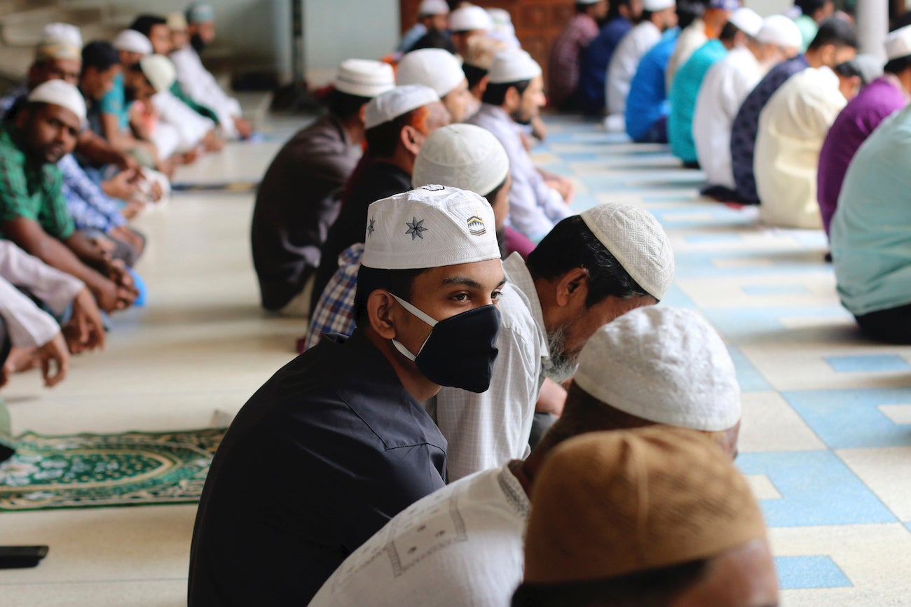 Muslims wear protective masks while offering Friday prayers