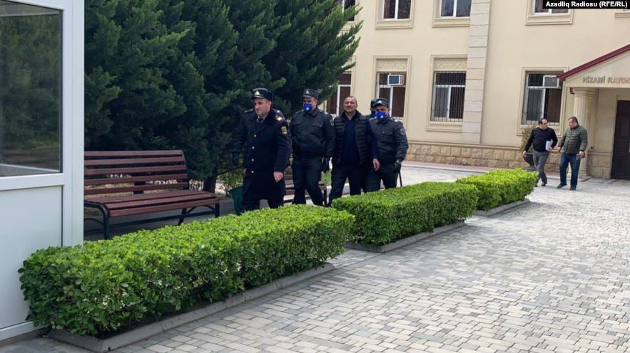 Policemen bringing the opposition leader Tofig Yagublu to Nizami District Court of Baku.