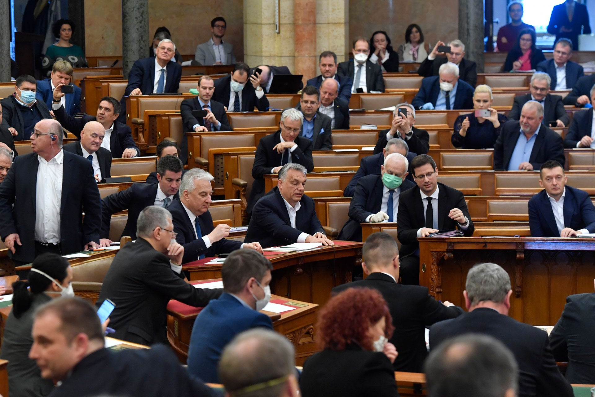 Hungarian Prime Minister Viktor Orban, center, his deputy Zsolt Semjen and other government members and MPs of the governing Fidesz party vote on a draft law concerning extraordinary measures during the plenary session of Parliament in Budapest, Hungary,