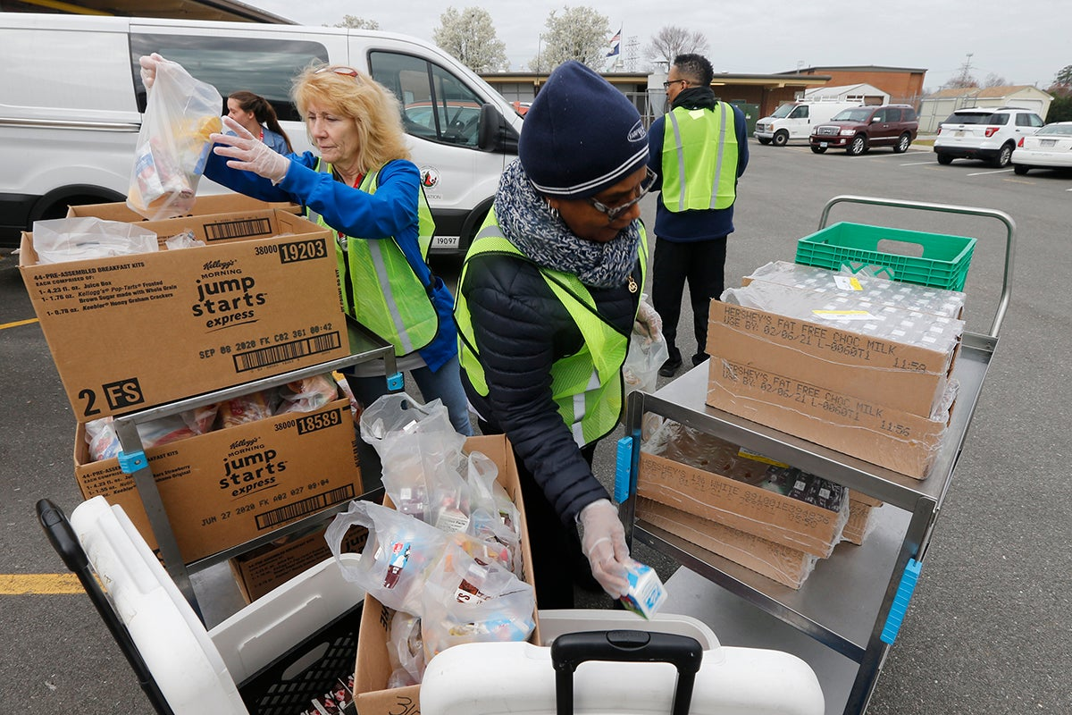 School workers load food packs as they distribute meals to students at Fairfield Middle School in Richmond, Virginia, March 18, 2020.
