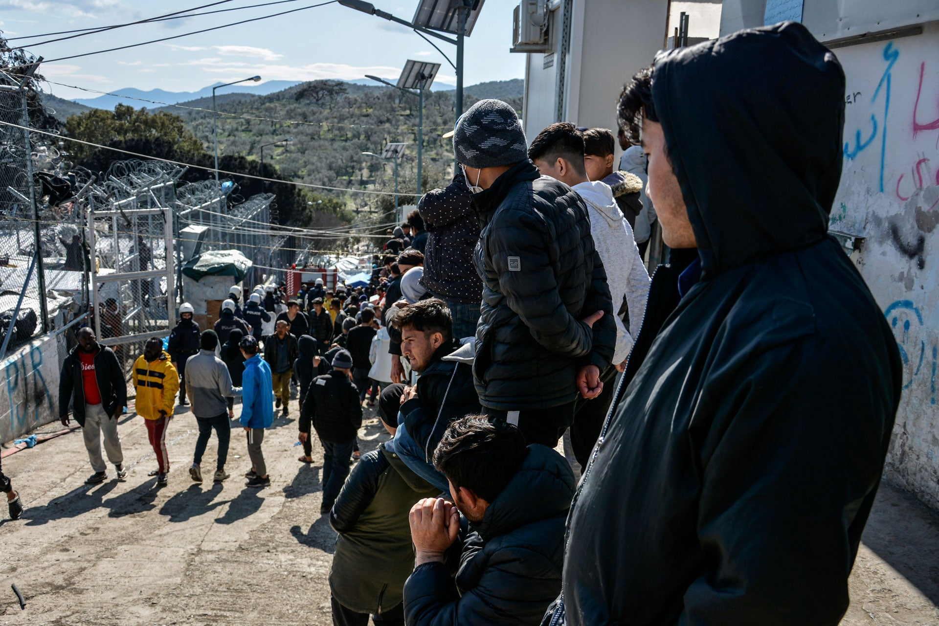 Migrants gather as riot police guard a gate in Moria refugee camp on the northeastern Aegean island of Lesbos, Greece, March 16, 2020.
