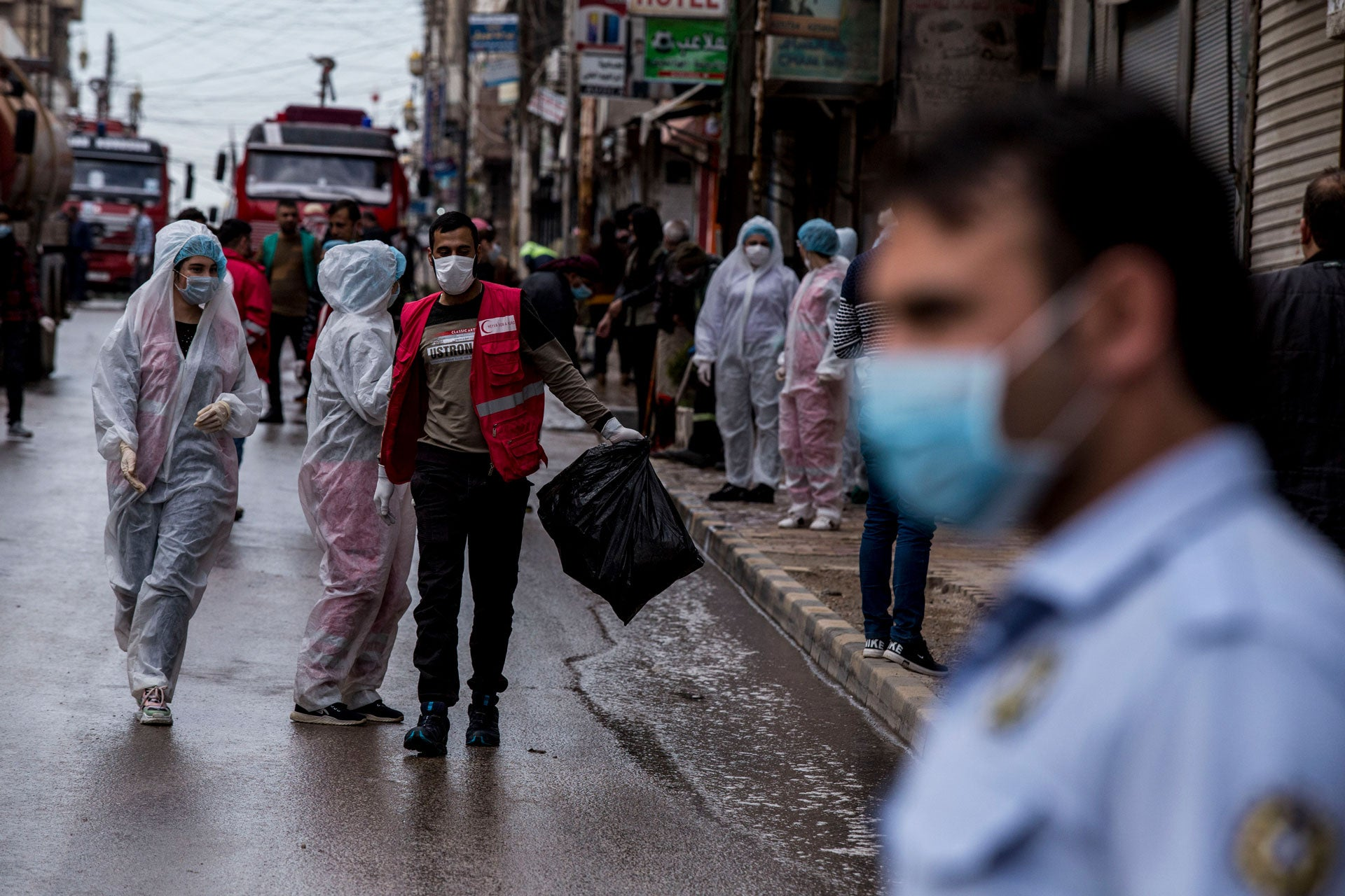 Medical workers oversee the disinfection of streets to prevent the spread of coronavirus in Qamishli, Syria, March 24, 2020.