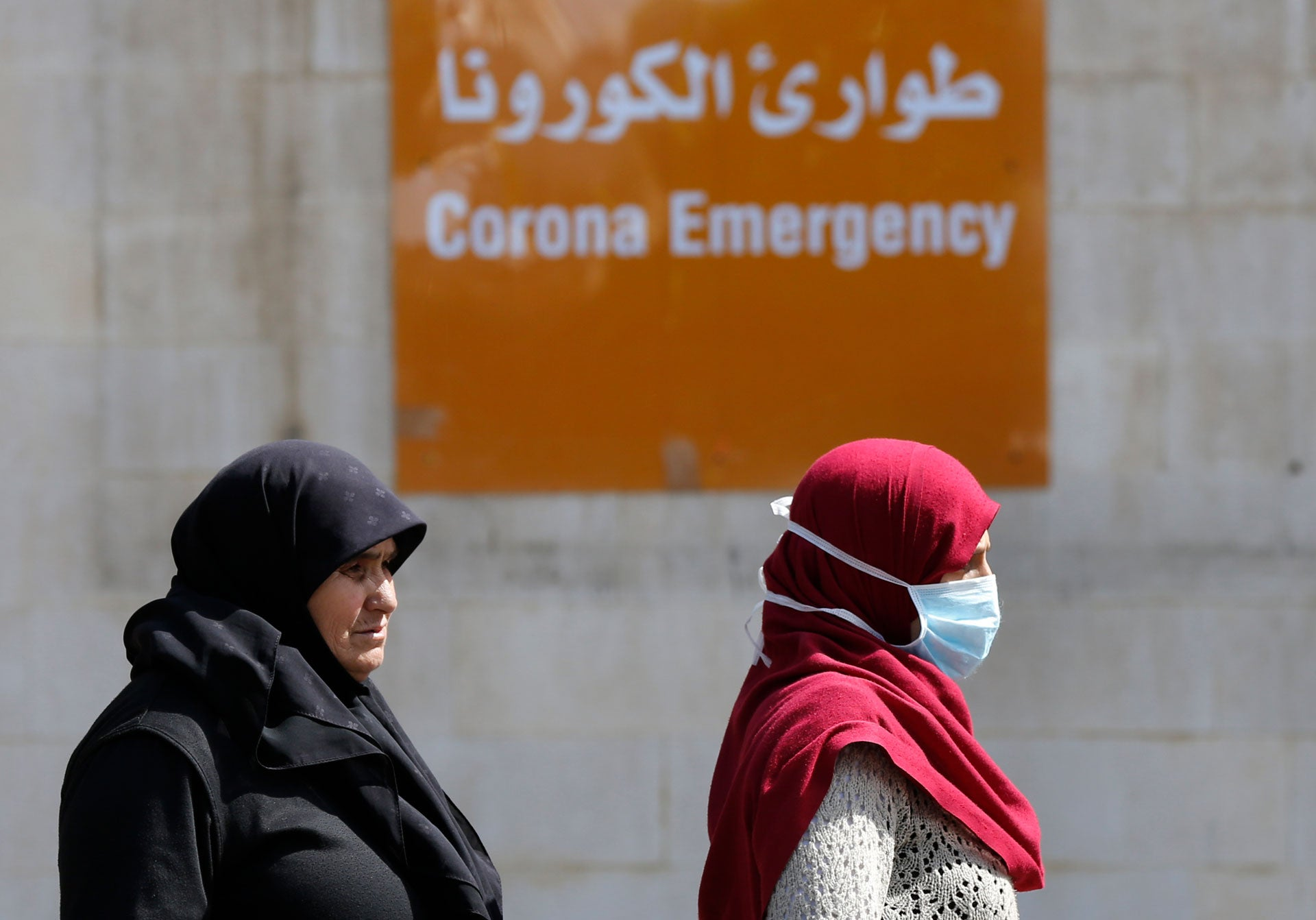 People pass in front the emergency entrance of the government-run Rafik Hariri University Hospital, where most of the Lebanese coronavirus cases are treated, in Beirut, Lebanon, March 11, 2020.