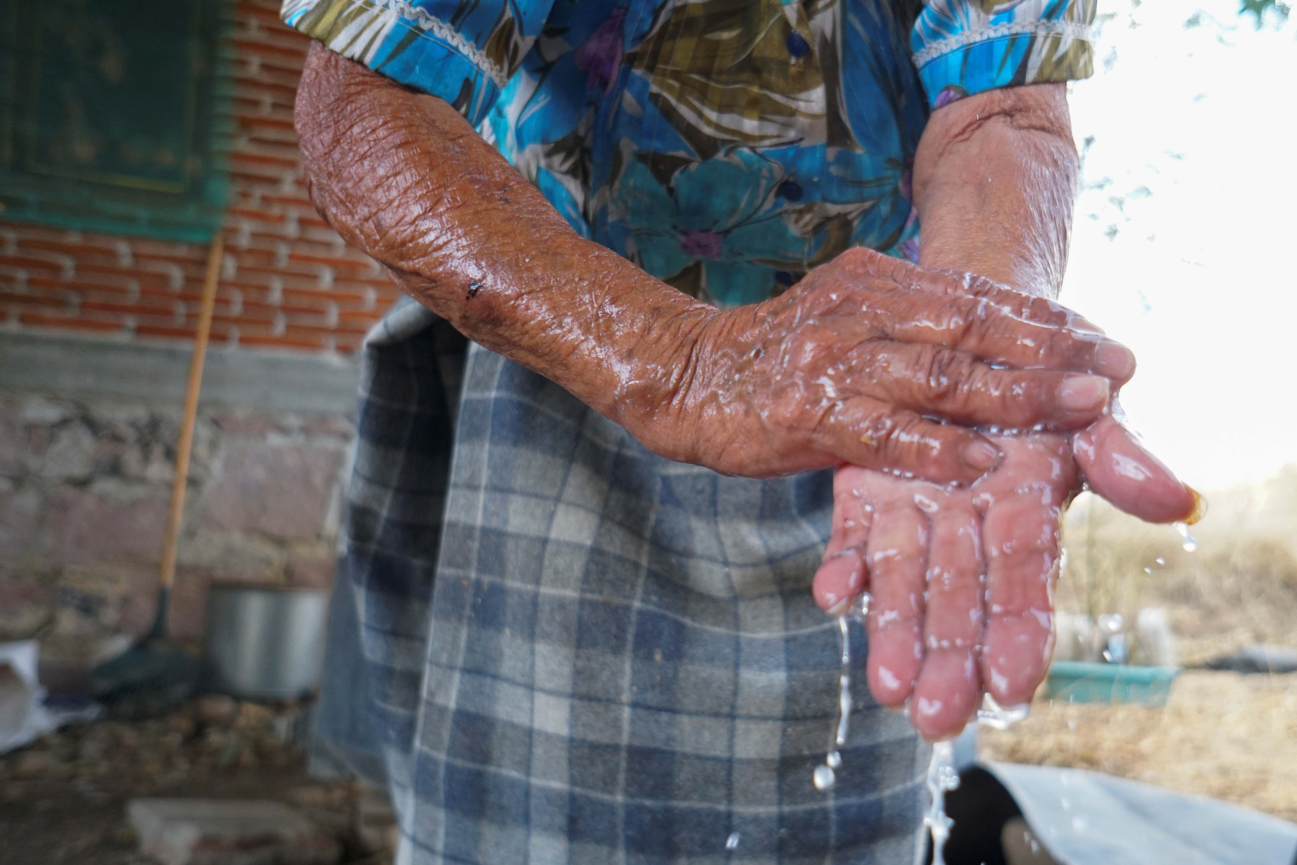 A Zapotec woman washes her hands after learning from a local radio program about hand-washing and social distancing to avoid COVID-19, in Oaxaca state, Mexico, March 31, 2020.