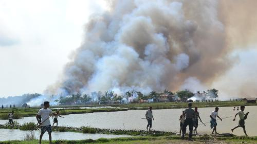 Ethnic Arakanese with weapons walking away from a village in flames while a soldier stands by. Arakan State, Burma, June 2012.