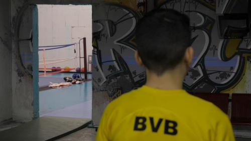 Boy in boxing gym with back towards camera