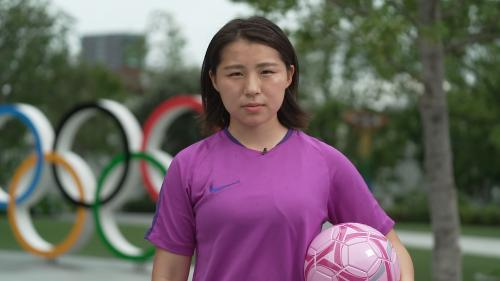 Soccer player holding ball in front of Olympic rings