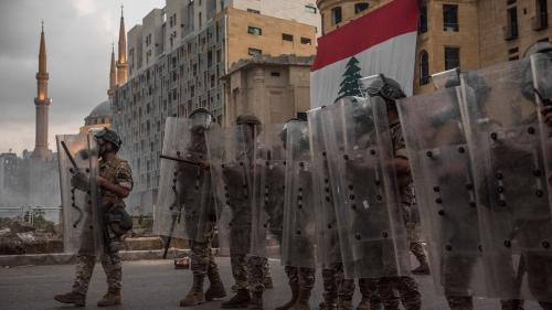 Riot police with shields in front of Lebanese flag