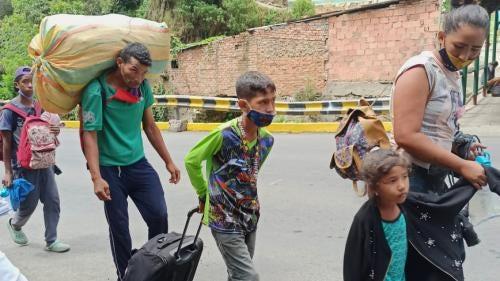 Returnees walking along road carrying belongings