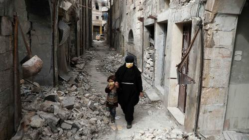 Woman and child in rubble in Idlib
