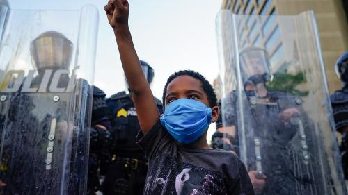 Child raises fist in front of line of police