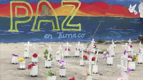 Mural that reads 'Paz en Tumaco' with graves/memorials in the foreground