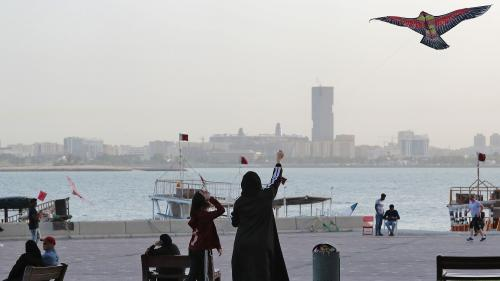 Women fly a kite in a park next to a body of water