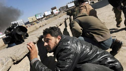 Afghan journalists seek cover in Kabul on Jan. 18, 2010 during a series of co-ordinated attacks by Taliban militants in the Afghan capital that killed at least 10 people and injured 32.