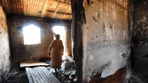 A woman walks through a house that was burned during the January 19, 2010 attack on Kuru Karama, Plateau State, which left more than 170 Muslims dead.