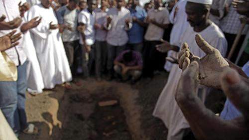 Sudanese men at the funeral of Salah Sanhouri, 26, who was killed during protests by security forces on September 27, 2013, pray over his body. Protests over subsidy cuts on fuel and food have been taking place across Sudan since September 2013.