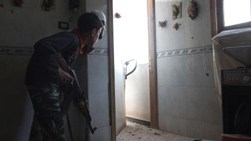 A 14-year-old fighter in a Free Syrian Army brigade takes position inside a house in Deir al-Zor, a city in eastern Syria, in July 2013.