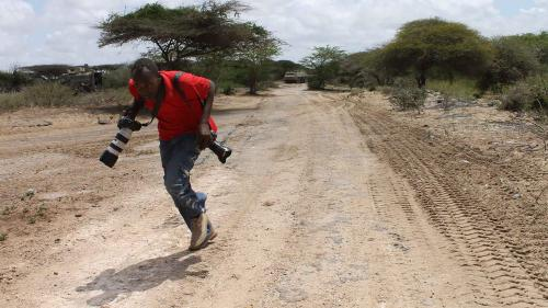 Somali photojournalist runs for cover while reporting on fighting between the Somali government and African Union forces against the Islamist armed group Al-Shabab in the Lower Shabelle region of Somalia, April 2012.