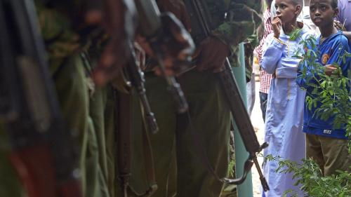A picture of children looking at Kenyan police carrying guns.