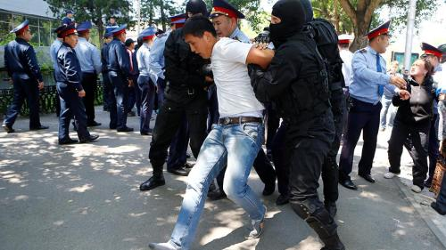 Police arrest protester in Kazakhstan.
