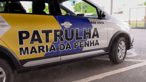 "A close-up of a Brazilian police car with the words ""Patrulha Maria da Pena"" on its side."