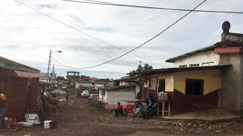 A wide shot of houses in a neighborhood of Malabo, Equatorial Guinea, with unpaved roads, one-storey houses, and trash