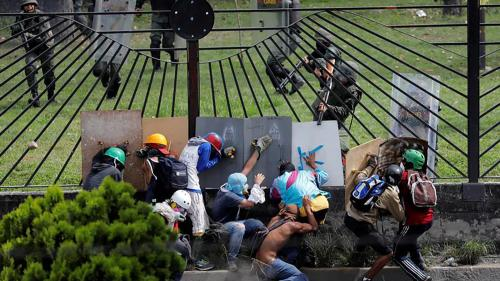 Demonstrators clash with riot security forces at the fence of an air base while rallying against Venezuela's President Nicolas Maduro in Caracas, Venezuela.