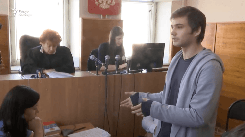 A young man in a hoodie stands in a courtroom speaking to the judges.