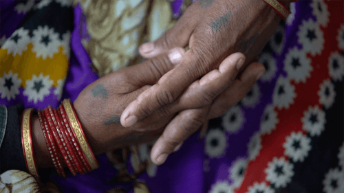 A close-up photo showing the hands of a sexual violence victim in India.