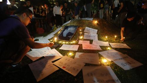 "People light candles next to signs at a vigil in solidarity with protesters of the ""Occupy Central"" movement in Hong Kong, at Speakers' Corner in Hong Lim Park, Singapore, on October 1, 2014."