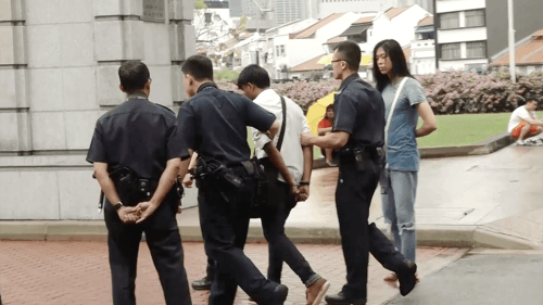 Photo of an activist being arrested in Singapore.
