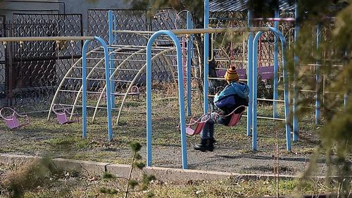 A boy sits on a swing in the courtyard of an orphanage for children with disabilities, Yerevan, Armenia.