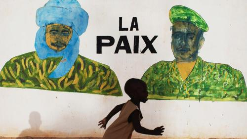 "A boy in Timbuktu runs in front of a mural that reads ""Peace,"" a few days before the July 2013 presidential elections in Mali."