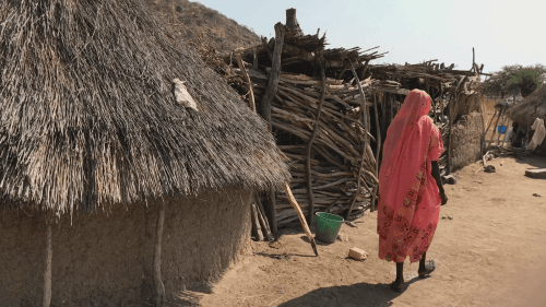 Woman walking besides huts.